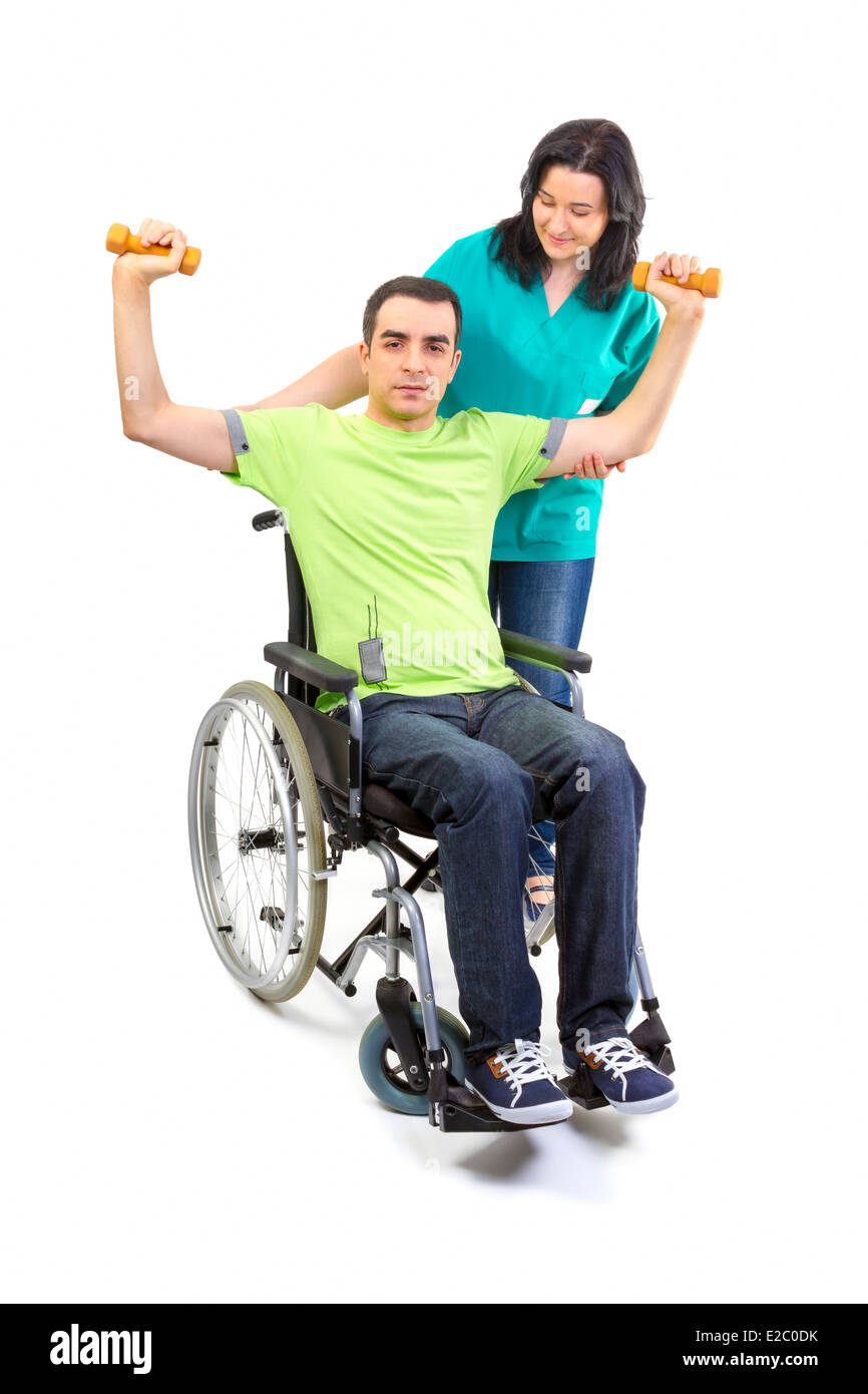 Physical therapist works with patient in lifting hands weights. Young adult in wheelchair. Stock Photo