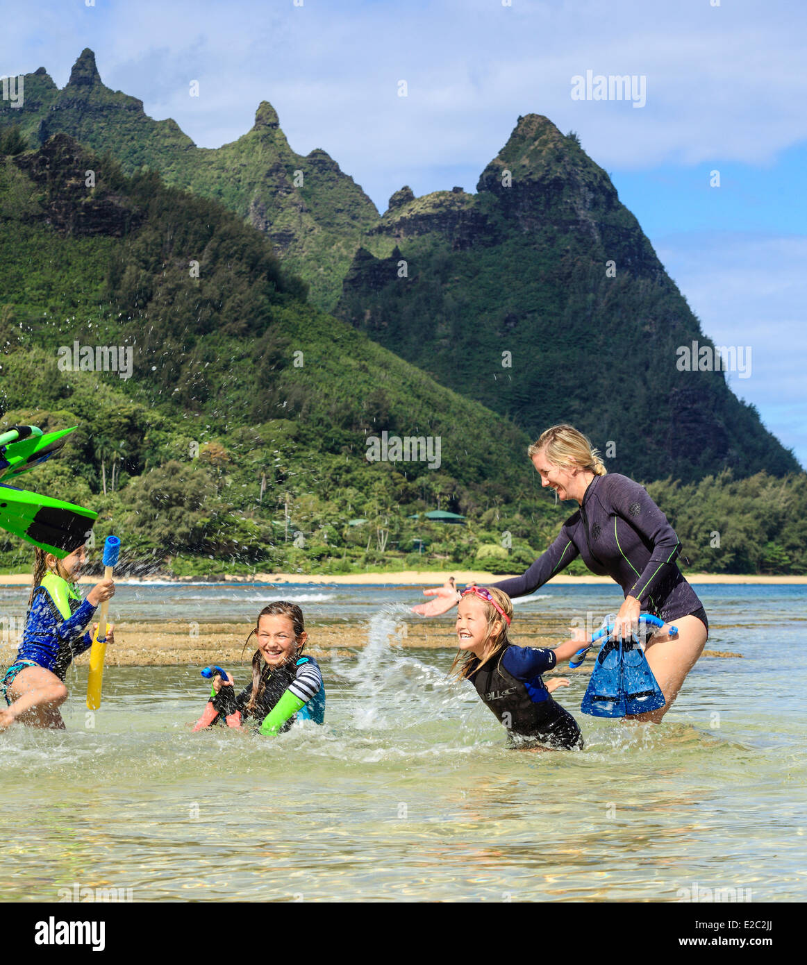Family having fun splashing each other at Tunnels Beach on Kauai - Stock Image