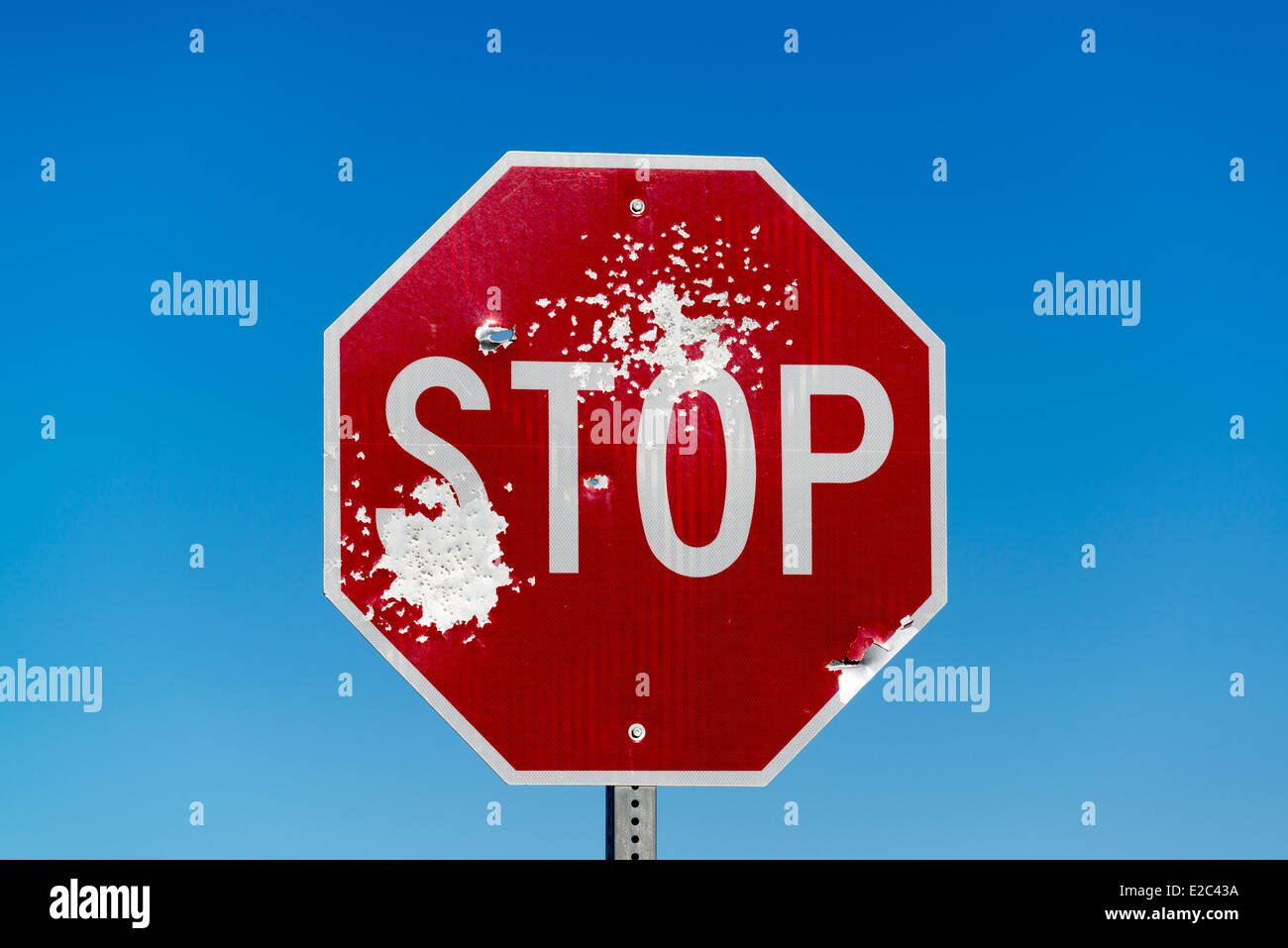 Bullet scarred stop sign. - Stock Image