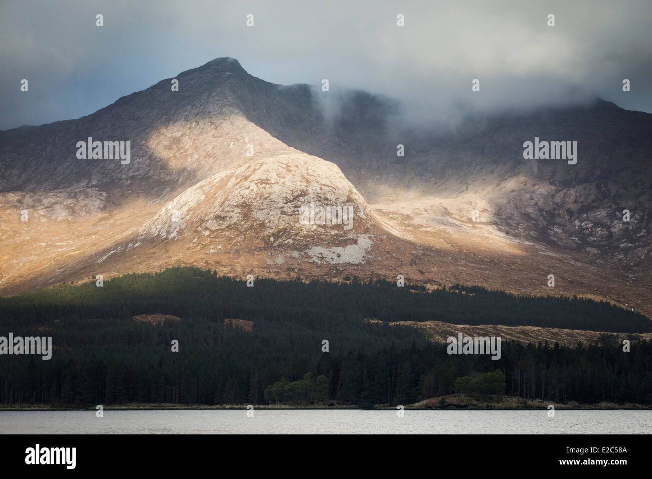 Sunlight rolling across the Derryclare hills and Lough Inagh Connemara County Galway Ireland Stock Photo