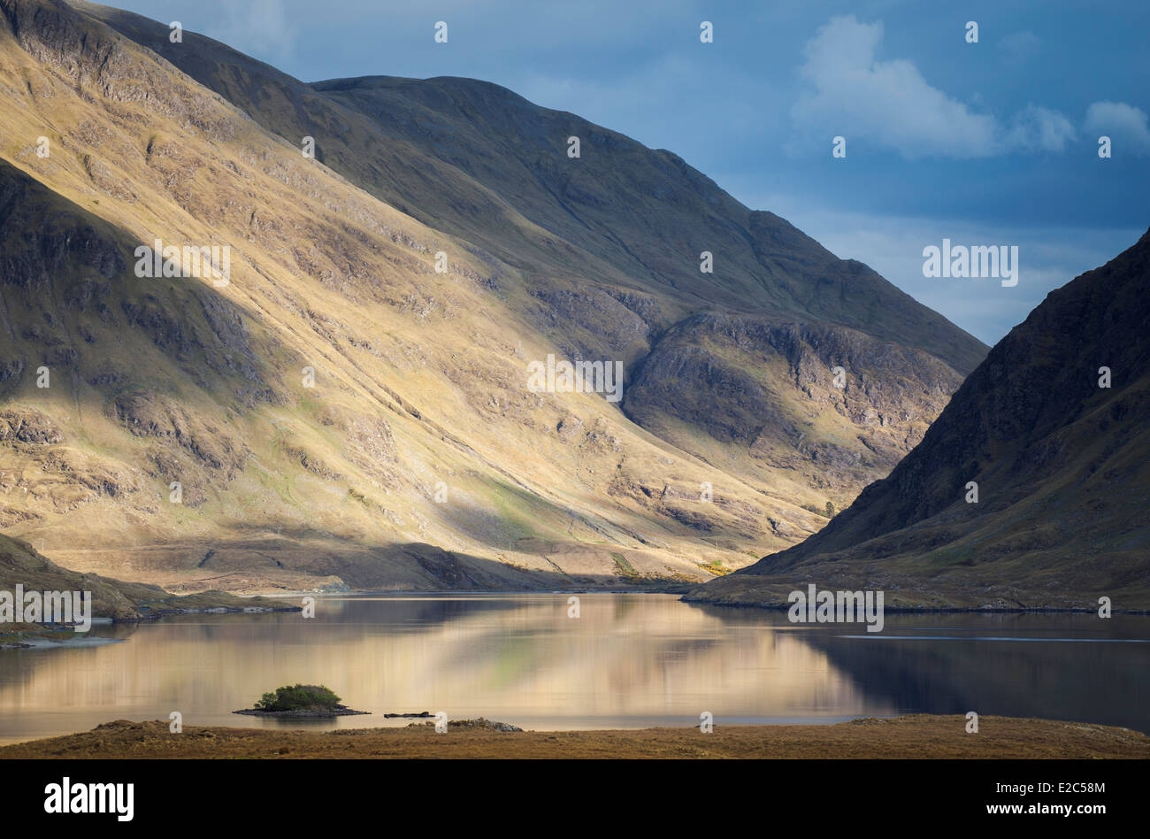Sunlight rolling across the hills surrounding and reflecting in Doo Lough County Mayo Ireland Stock Photo
