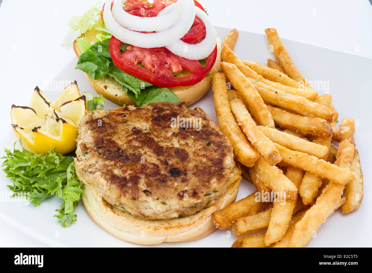 Pan fried crab cake sandwich served with a side of French fries. - Stock Image