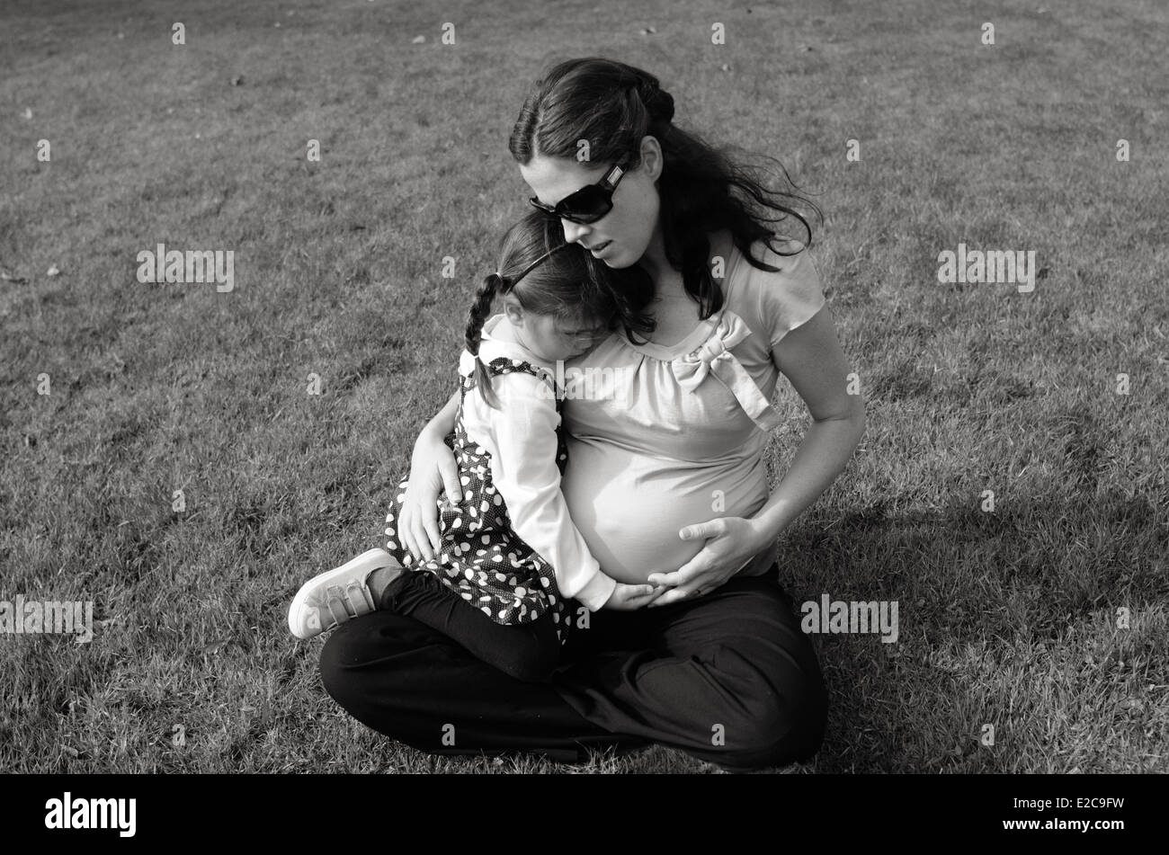 Pregnant woman hug her daughter during pregnancy outdoor at the park. - Stock Image
