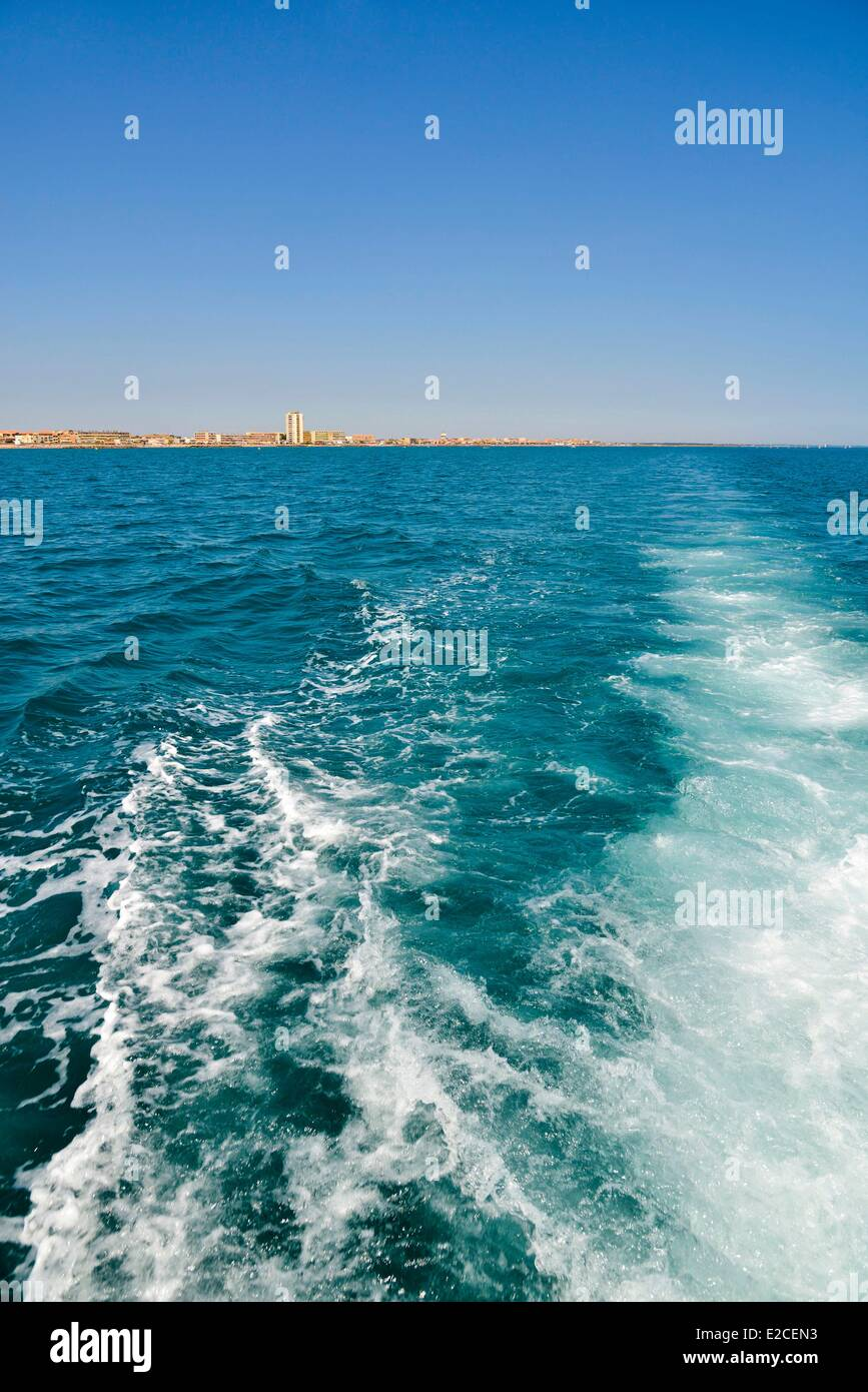 France, Herault, Valras Plage, foam produced by the trail of a motorboat with the background coast - Stock Image