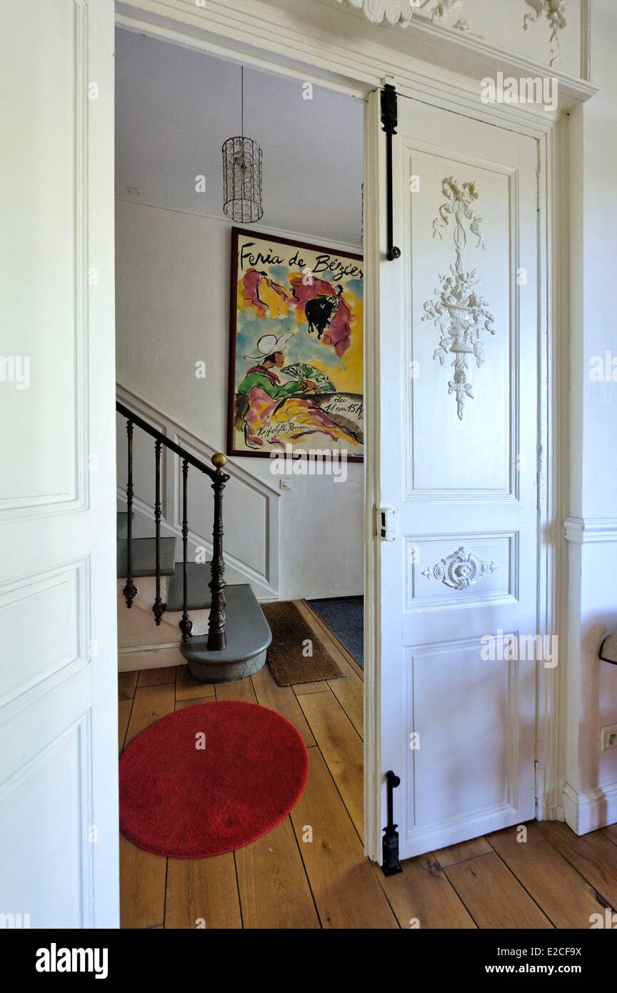 France, Herault, Beziers, Hotel of the Poets, the door of the hall with a straight staircase and a background poster - Stock Image