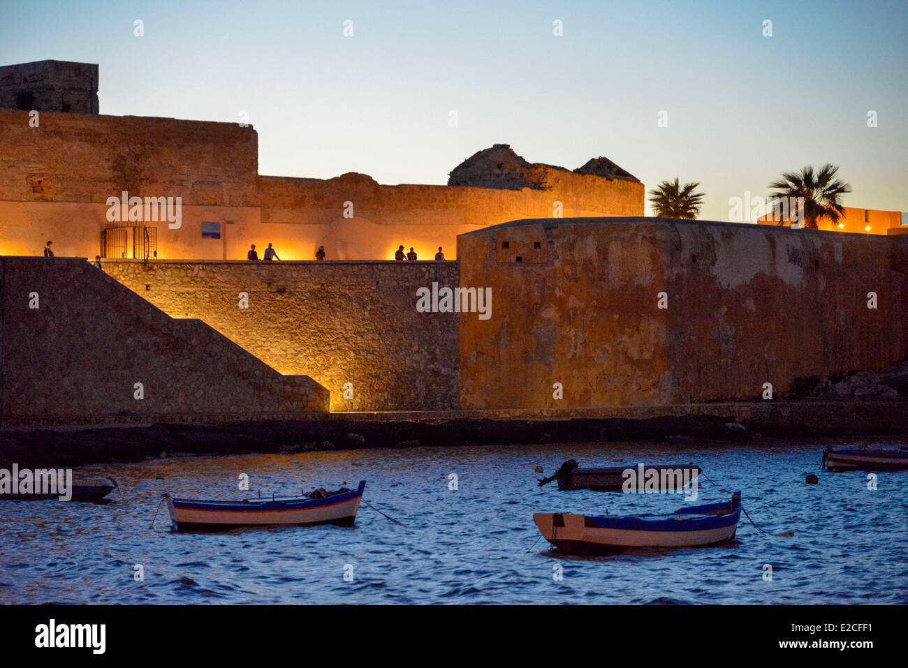 Italy, Sicily, Trapani, historic center, Conca fortress illuminated at dusk with boats on the water in the foreground - Stock Image