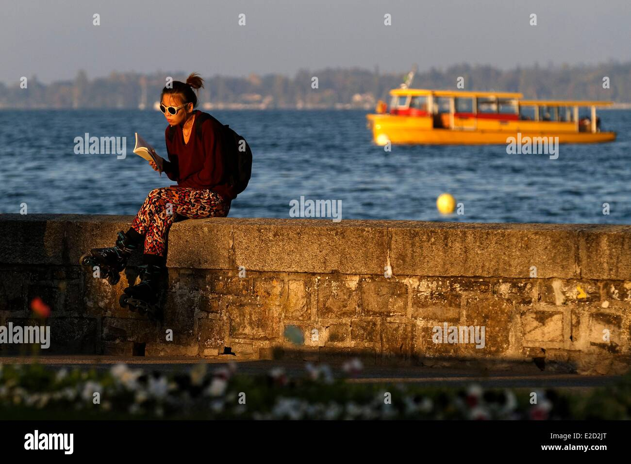 Switzerland Geneva Lake Geneva Parc Mon Repos young woman reading on the bank - Stock Image