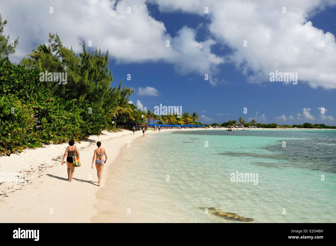 France Guadeloupe Saint Martin Le Galion two people walking towards the blue umbrellas lined up on the beach with - Stock Image