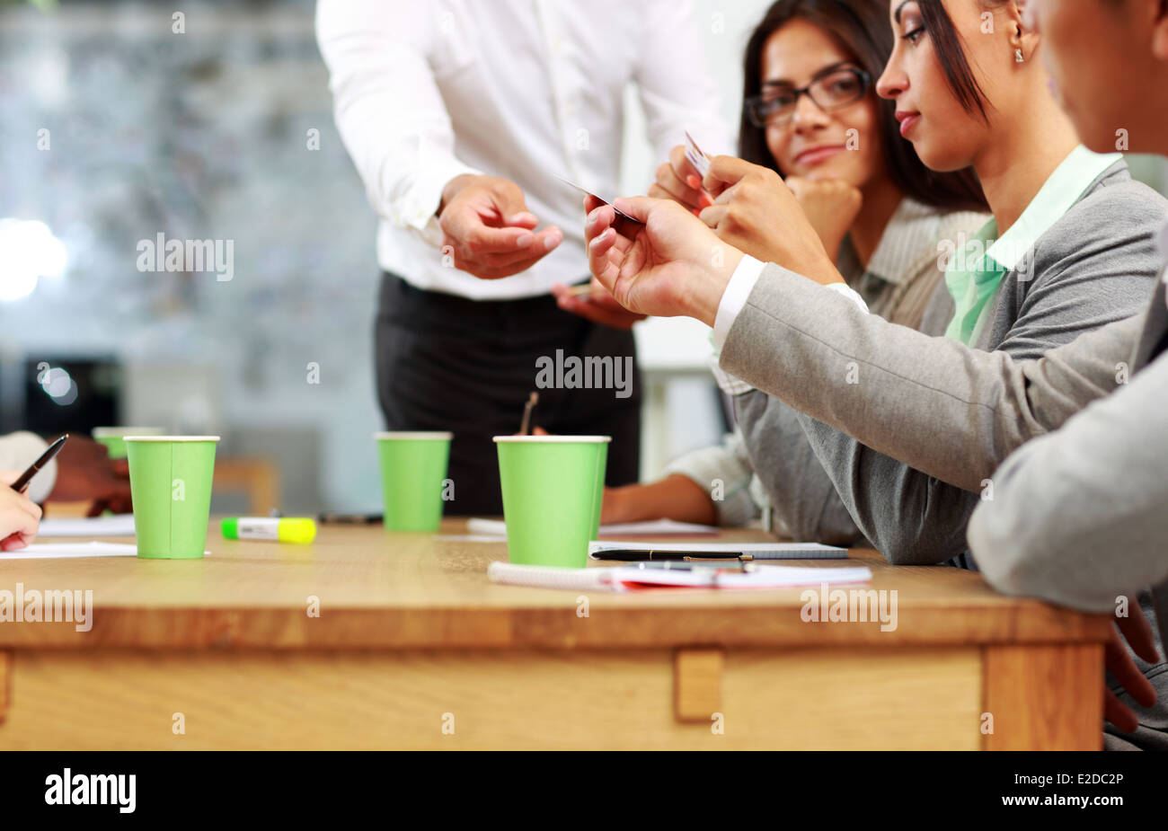 Businessman handing out a business card in meeting - Stock Image