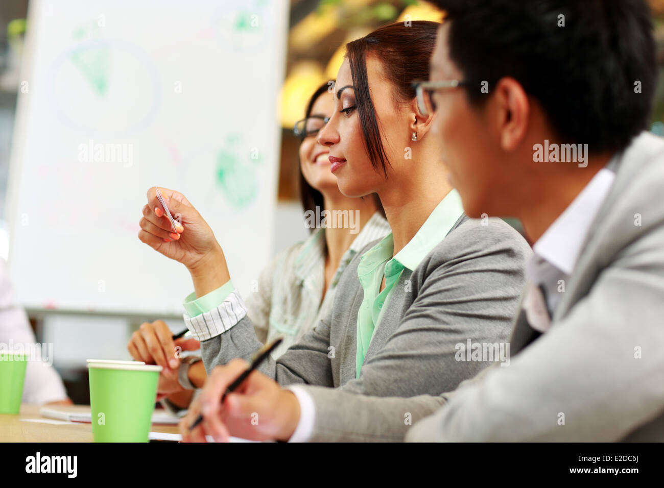 Businesswoman looking at business card in meeting - Stock Image