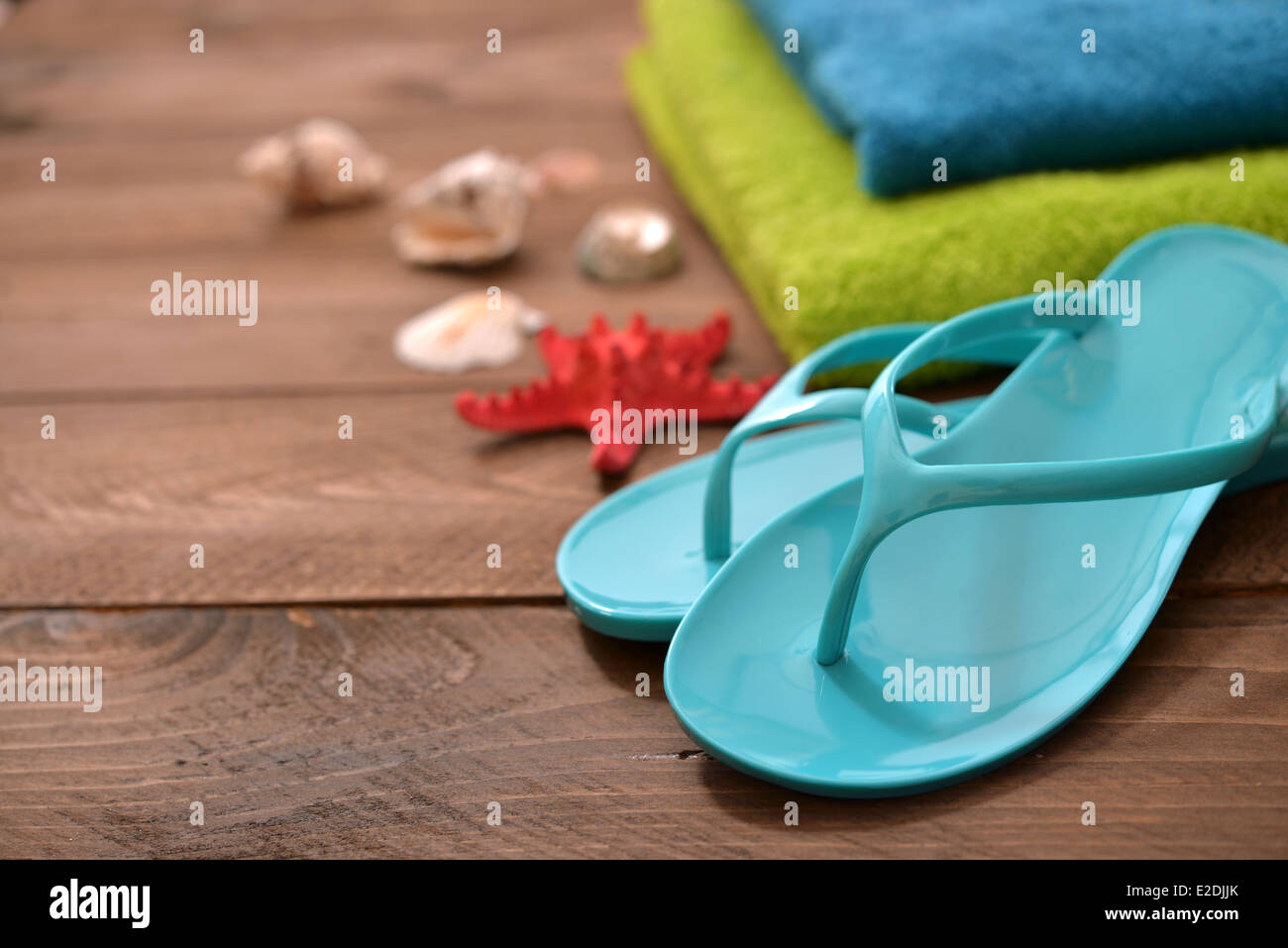 99b1cd061 Blue Flip-flops with red starfish and towel on wooden background - Stock  Image