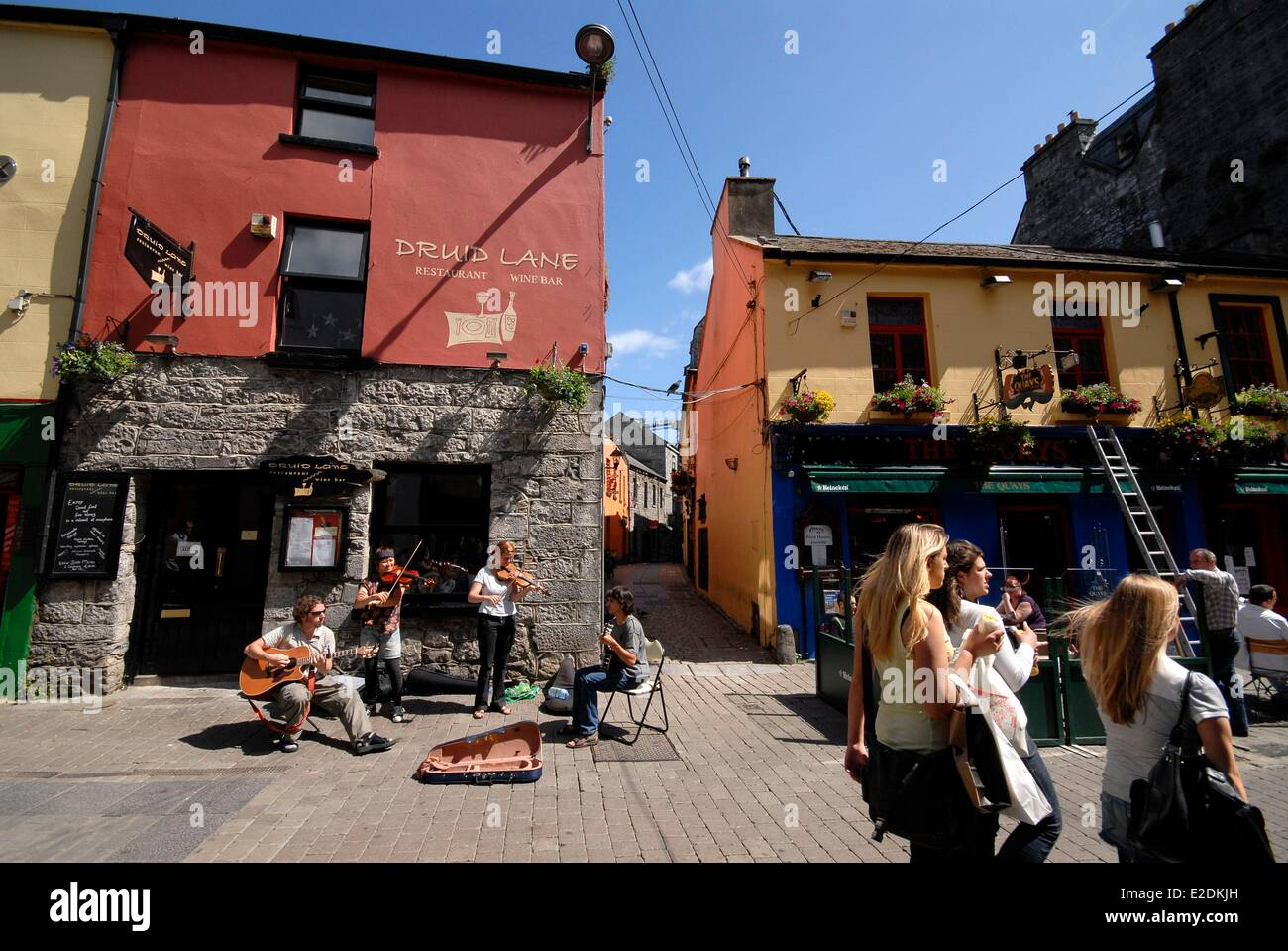 Ireland County Galway Galway pedestrian street with colorful houses street musicians - Stock Image