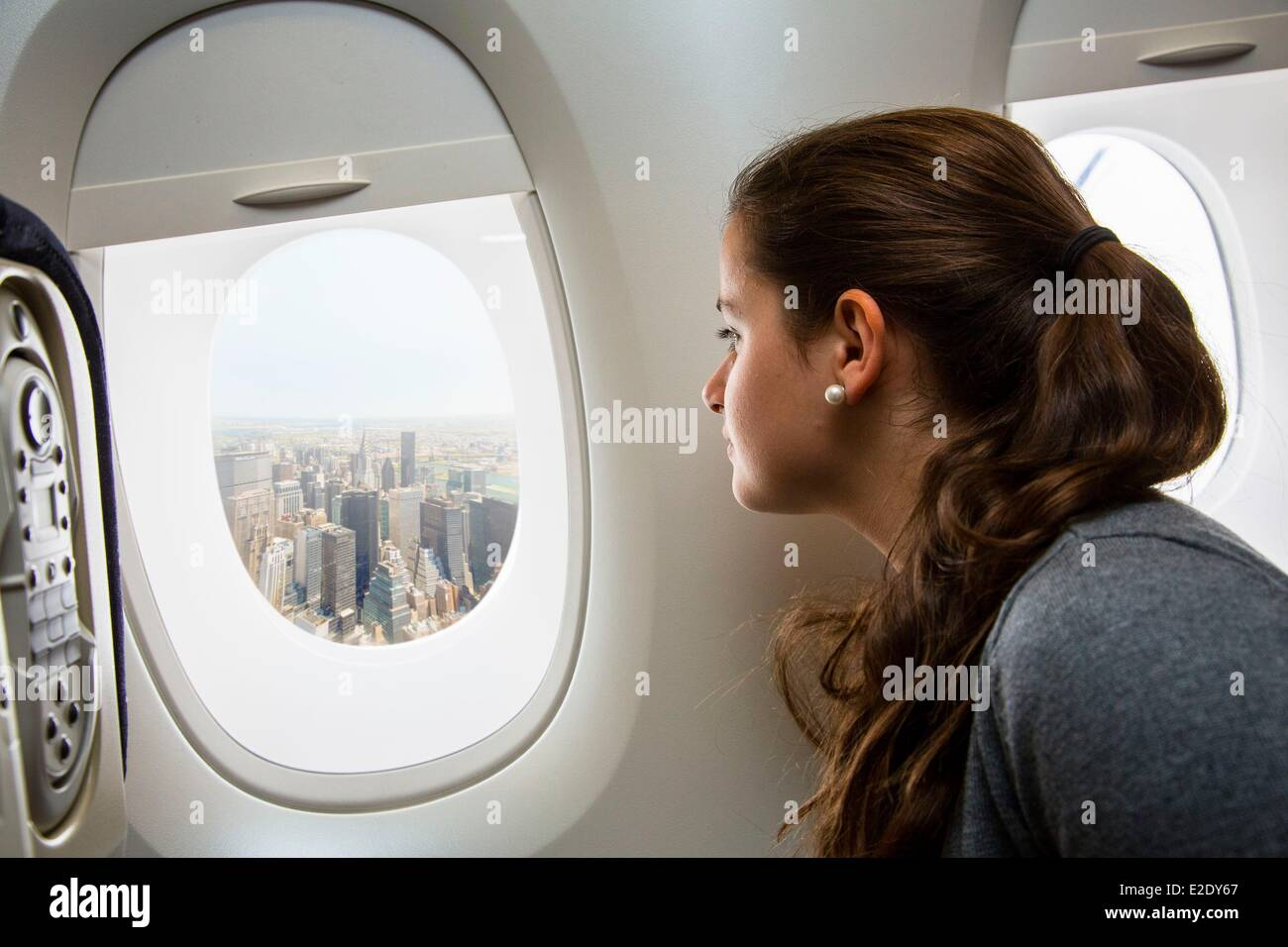United States long-haul flight between Paris and New York child looking out the window - Stock Image
