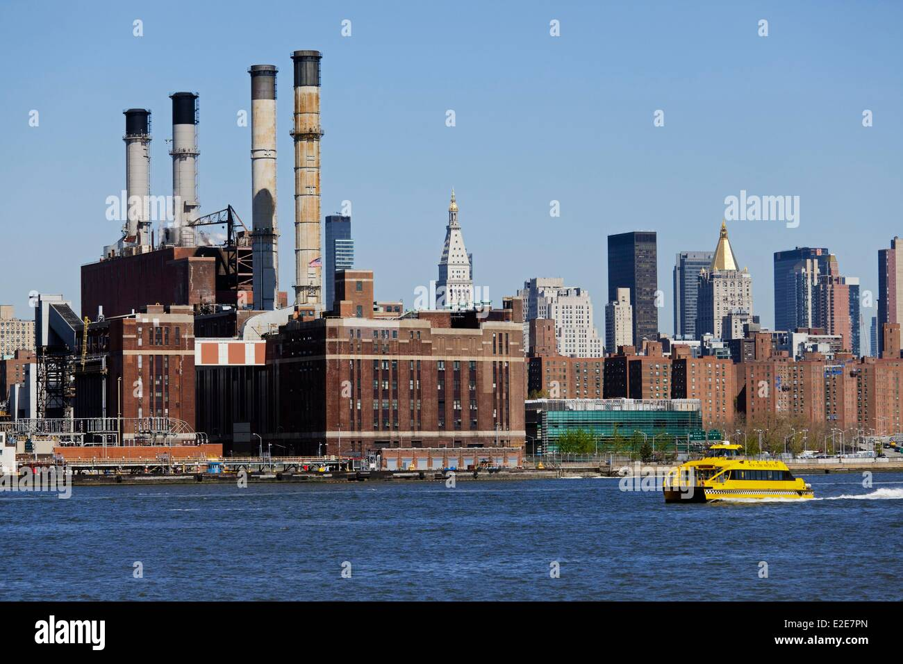 United States New York Manhattan Midtown from the East River yellow taxi boat in the background Consolidated Edison - Stock Image