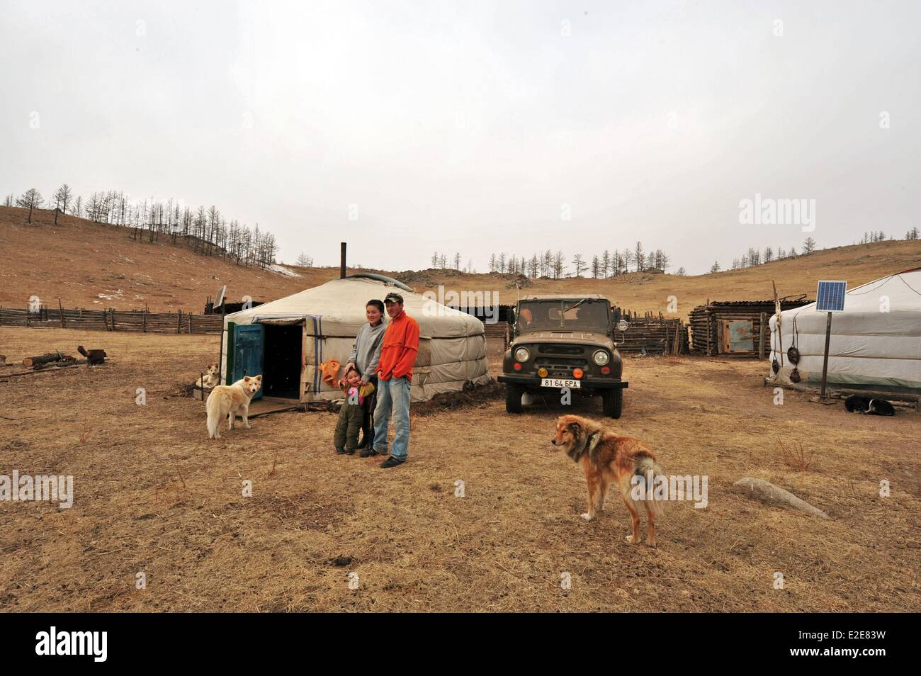Mongolia, Tov province, Baganuur, man and woman with daughter standing in front of a yurt by vehicle - Stock Image