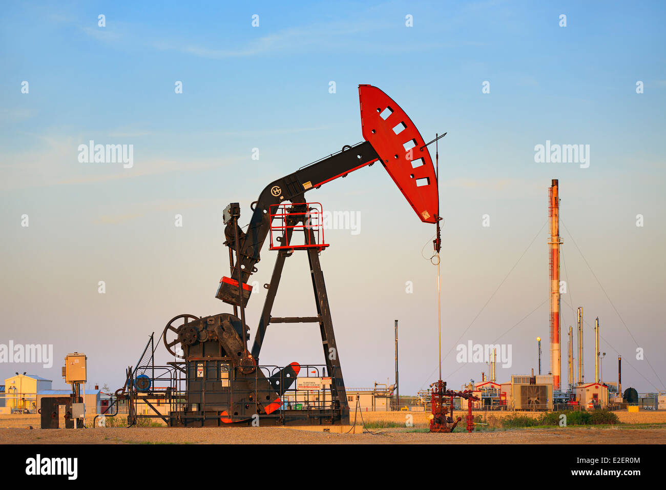 Oil well pump jack, with Liquid Natural Gas plant in background, near Estevan, Saskatchewan, Canada - Stock Image