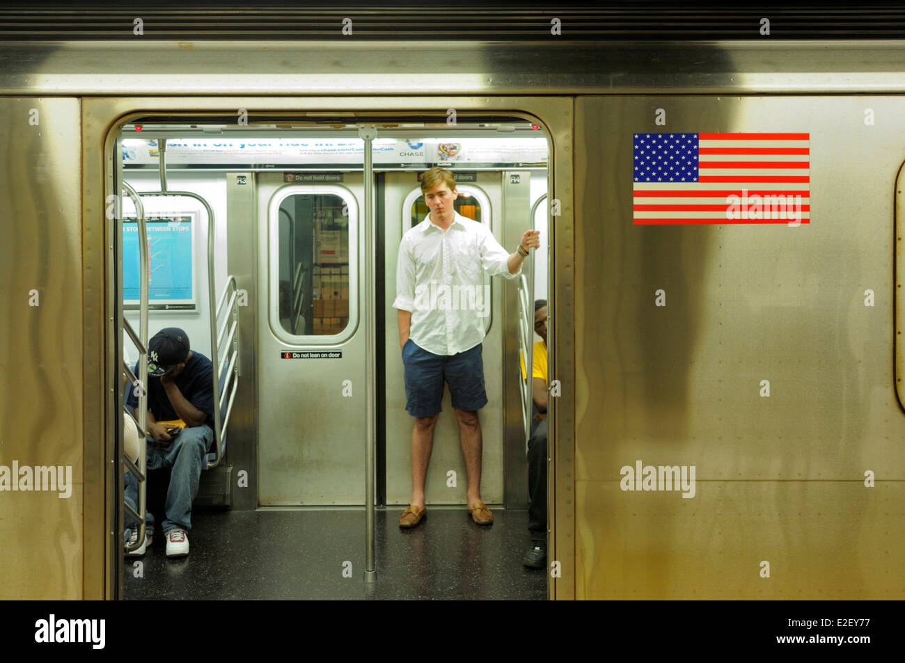 United States, New York, subway station in New York's 86th Street, a man in blue shorts and white shirt standing - Stock Image