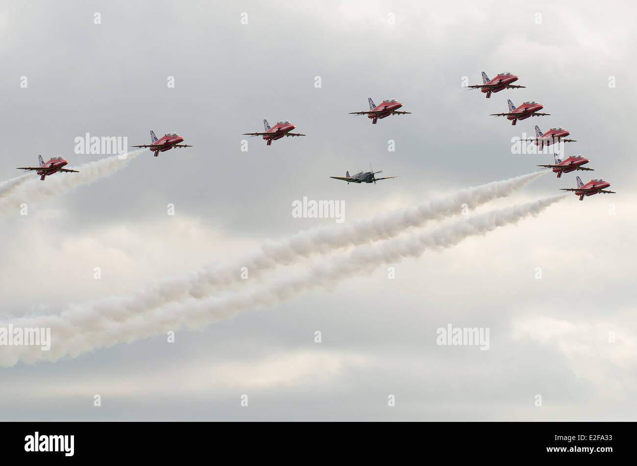 A formation to celebrate the Red Arrow's fiftieth display season. The team formate with a Spitfire. - Stock Image