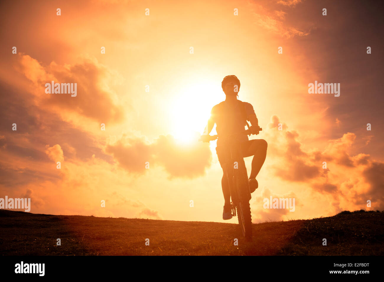 The silhouette of mountain bicycle rider on the hill - Stock Image