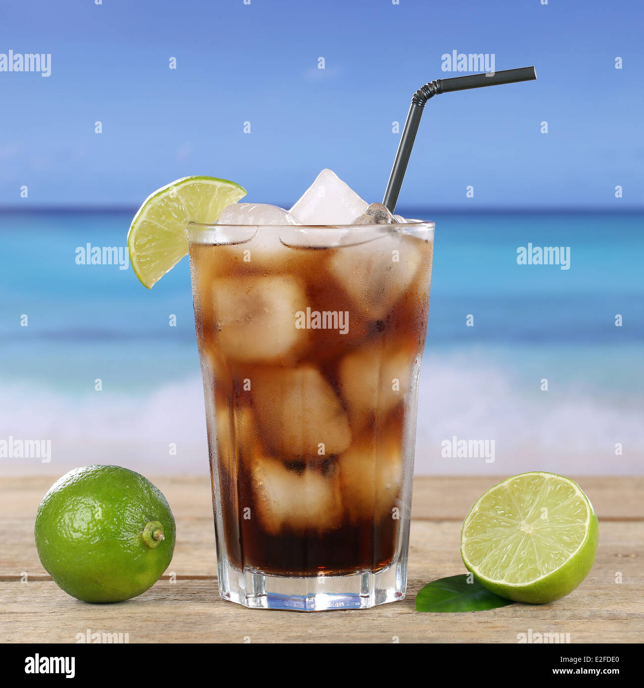 Cola or Cuba Libre cocktail drink in glass with ice cubes on the beach - Stock Image