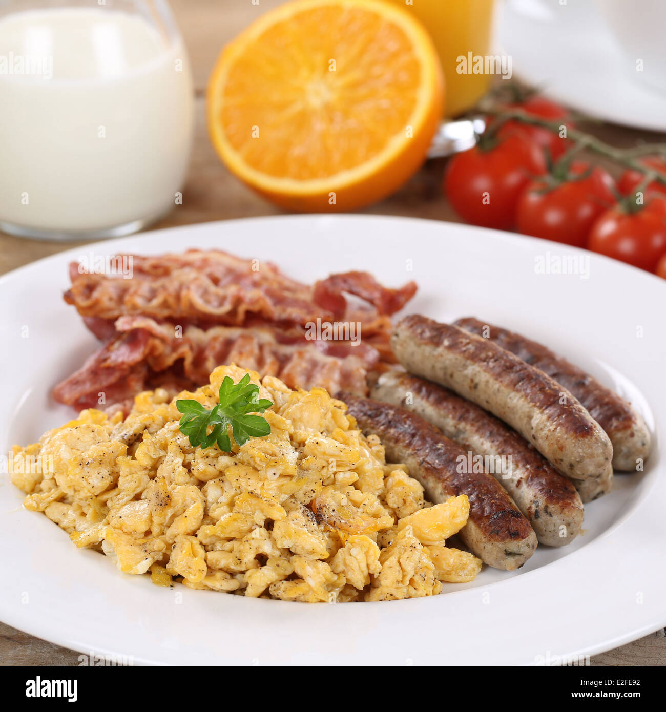 Meal with scrambled eggs, sausages, bacon, oranges and milk - Stock Image