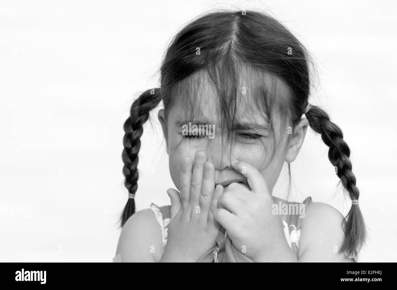Little girl (age 4) cries isolated on white background. Concept photo of child care, childhood, issues, emotion, - Stock Image