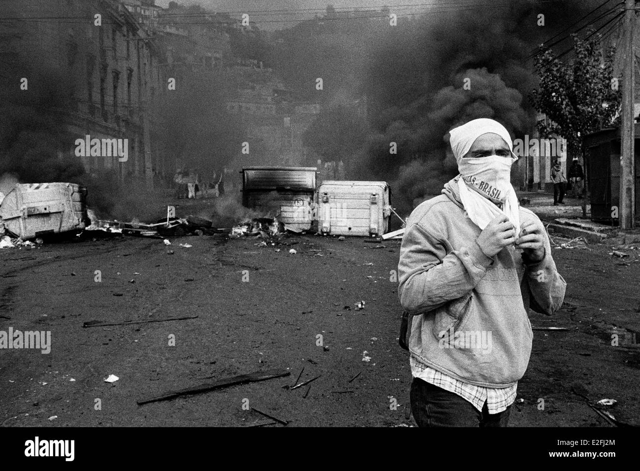 A Chilean student stands in front of the burning barricade during the anti-government protest in Valparaíso, - Stock Image