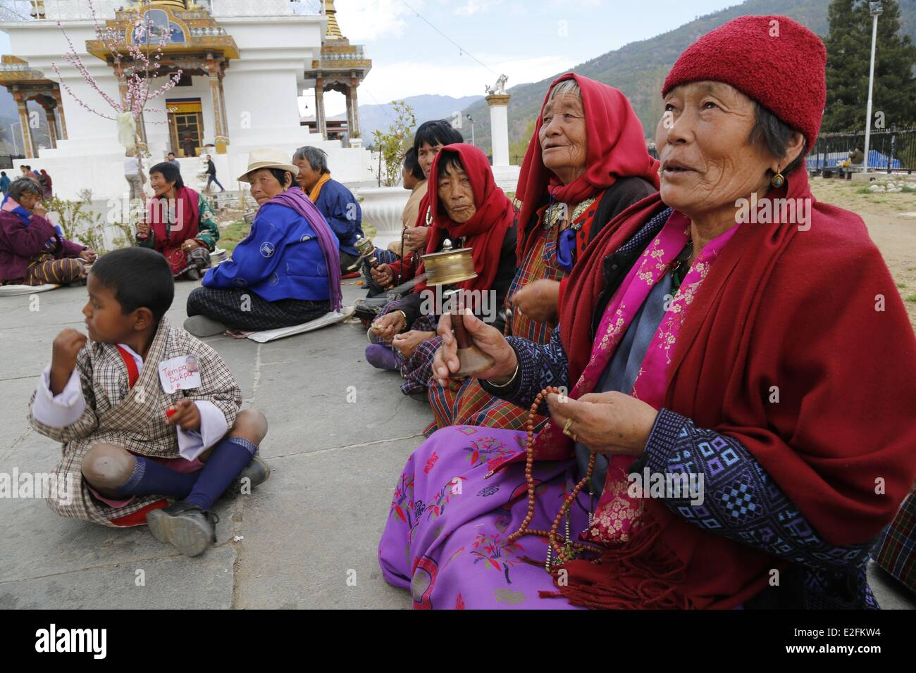 Bhutan Thimphu the Memorial buddhist chorten women praying for people who give some money - Stock Image