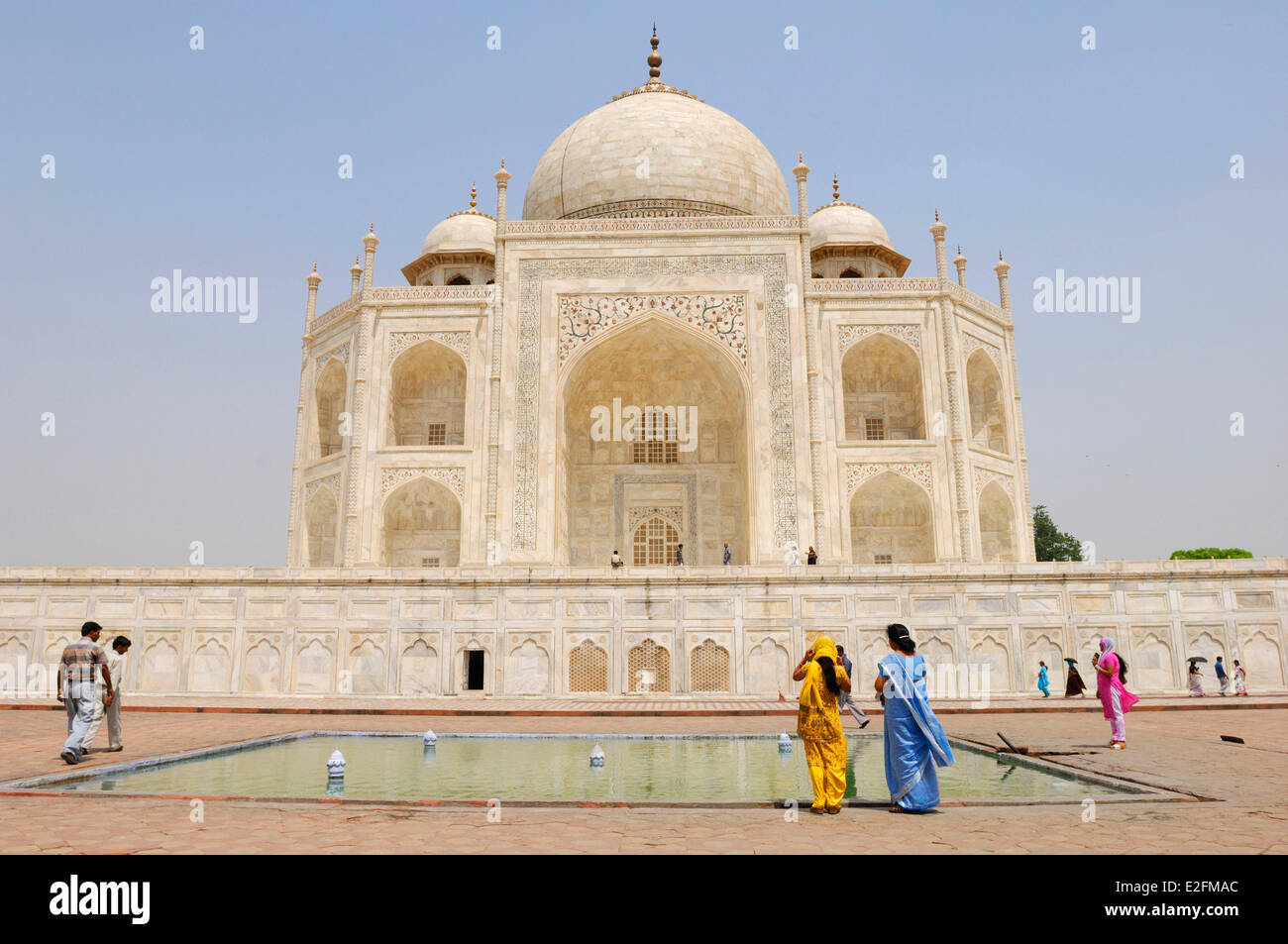 India Uttar Pradesh State Agra The Taj Mahal listed as World Heritage by UNESCO visitors from behind around a basin - Stock Image