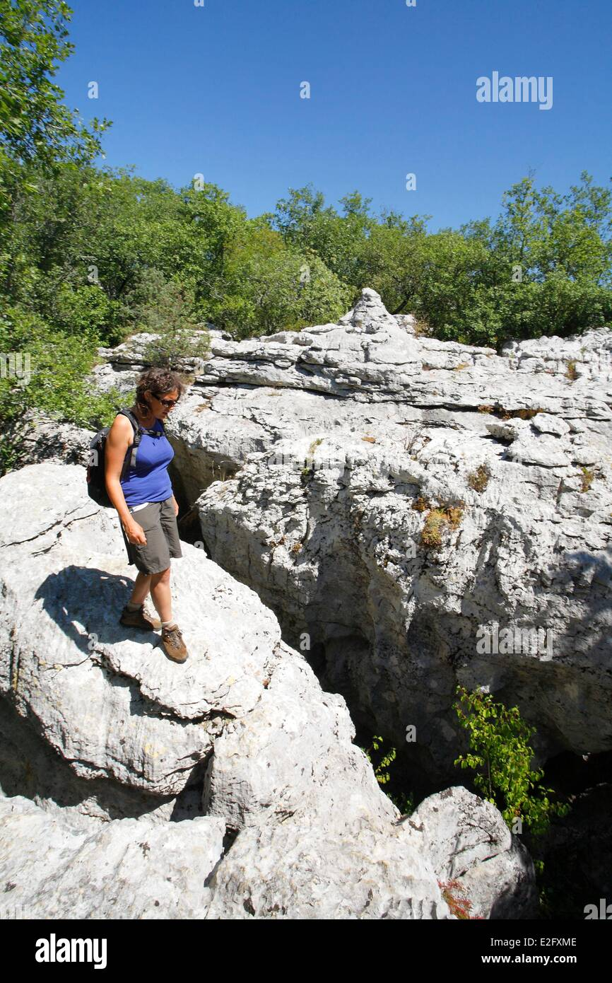 6725598881bc69 France Ardeche Les Vans Female hiker walking on rocks in the Paiolive wood  - Stock Image