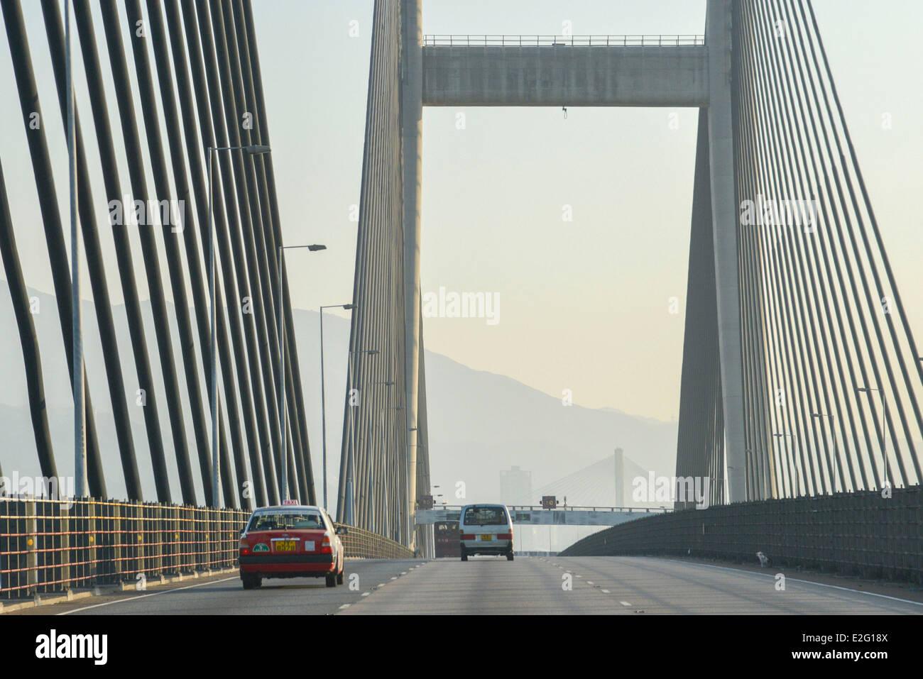 China Hong Kong Lantau Island red taxi on a highway exceeding the suspension bridge of Tsing Ma - Stock Image