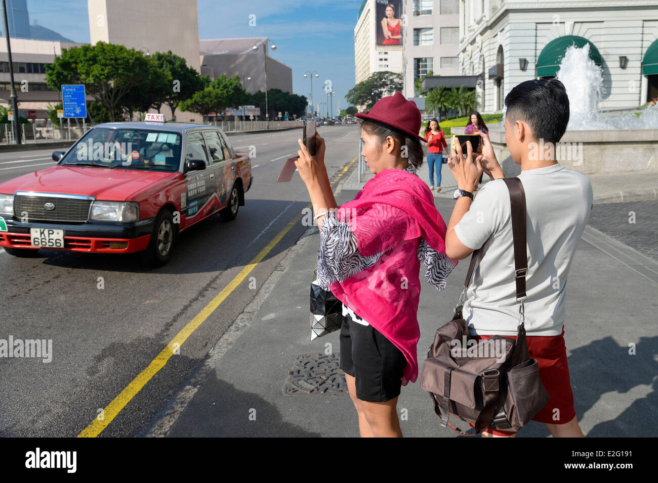 China Hong Kong Kowloon District couple of Asian tourists taking a photo with their mobile phone - Stock Image