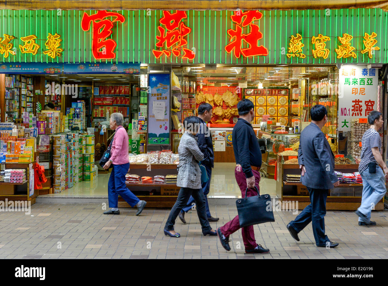 China Hong Kong Kowloon District Hankon Road go and come from pedestrians on a pavement passing in front of a Chinese - Stock Image