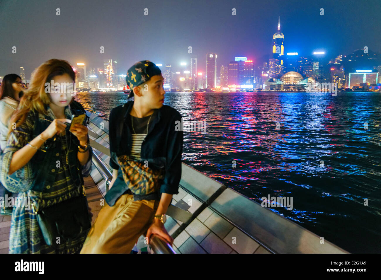 China Hong Kong Kowloon District Avenue of Stars girl consulting her mobile phone accompanied with a young man looking - Stock Image