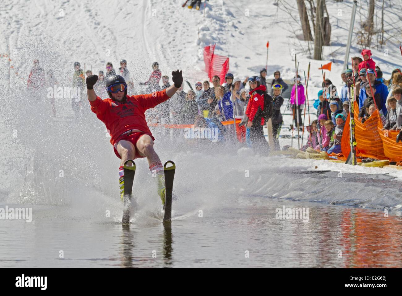 Canada Quebec province the Laurentians Morin Heights spring skiing event crossing the pond with ski - Stock Image