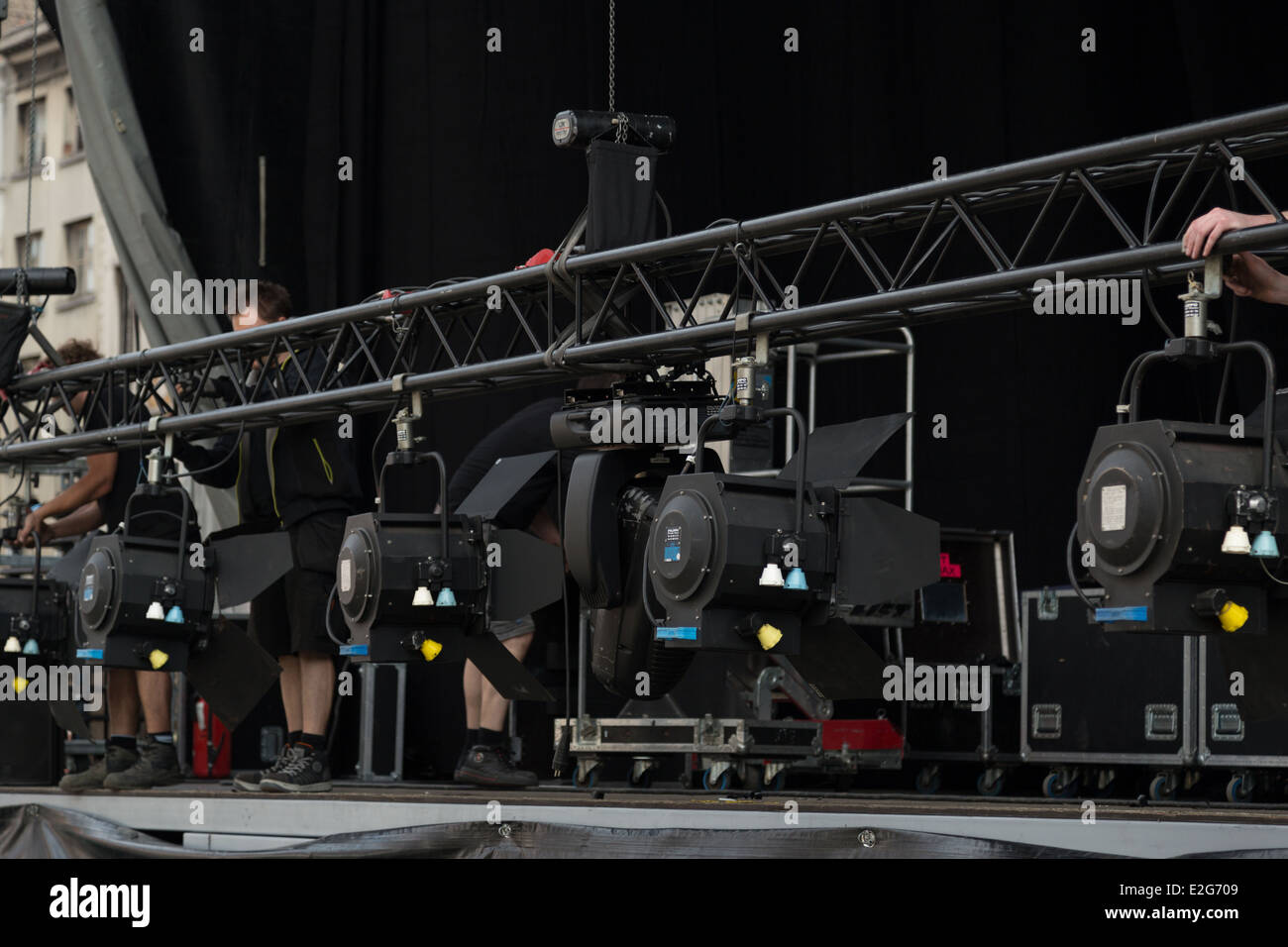 A photograph of some anonymous people setting up stage lighting for a band. - Stock Image