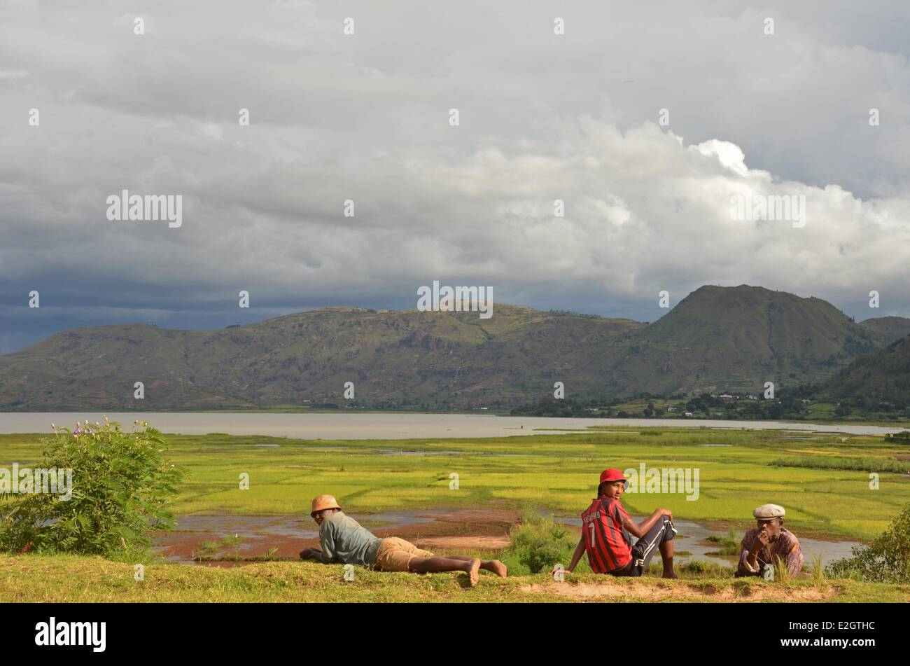 Madagascar Central Highlands Ampefy 3 malagasy men relaxing in front of Lake Itasy and ricefileds - Stock Image