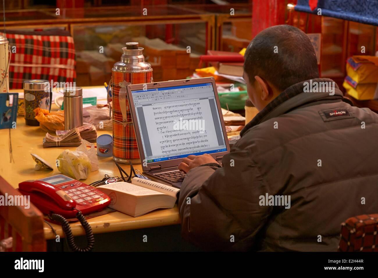 China Tibet Lhassa monk working on Buddist text on computer at Sera monastery - Stock Image