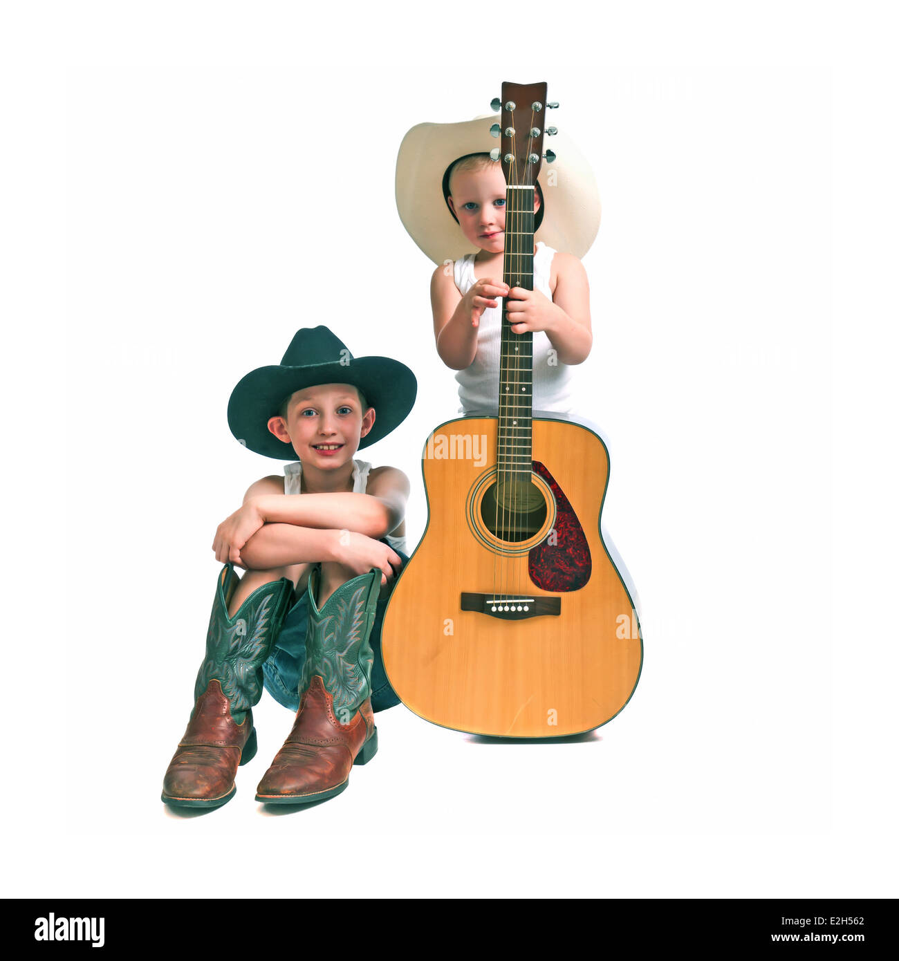 Pre-teen and a pre-schooler with cowboy hats , boots and a guitar, isolated against a white background. - Stock Image