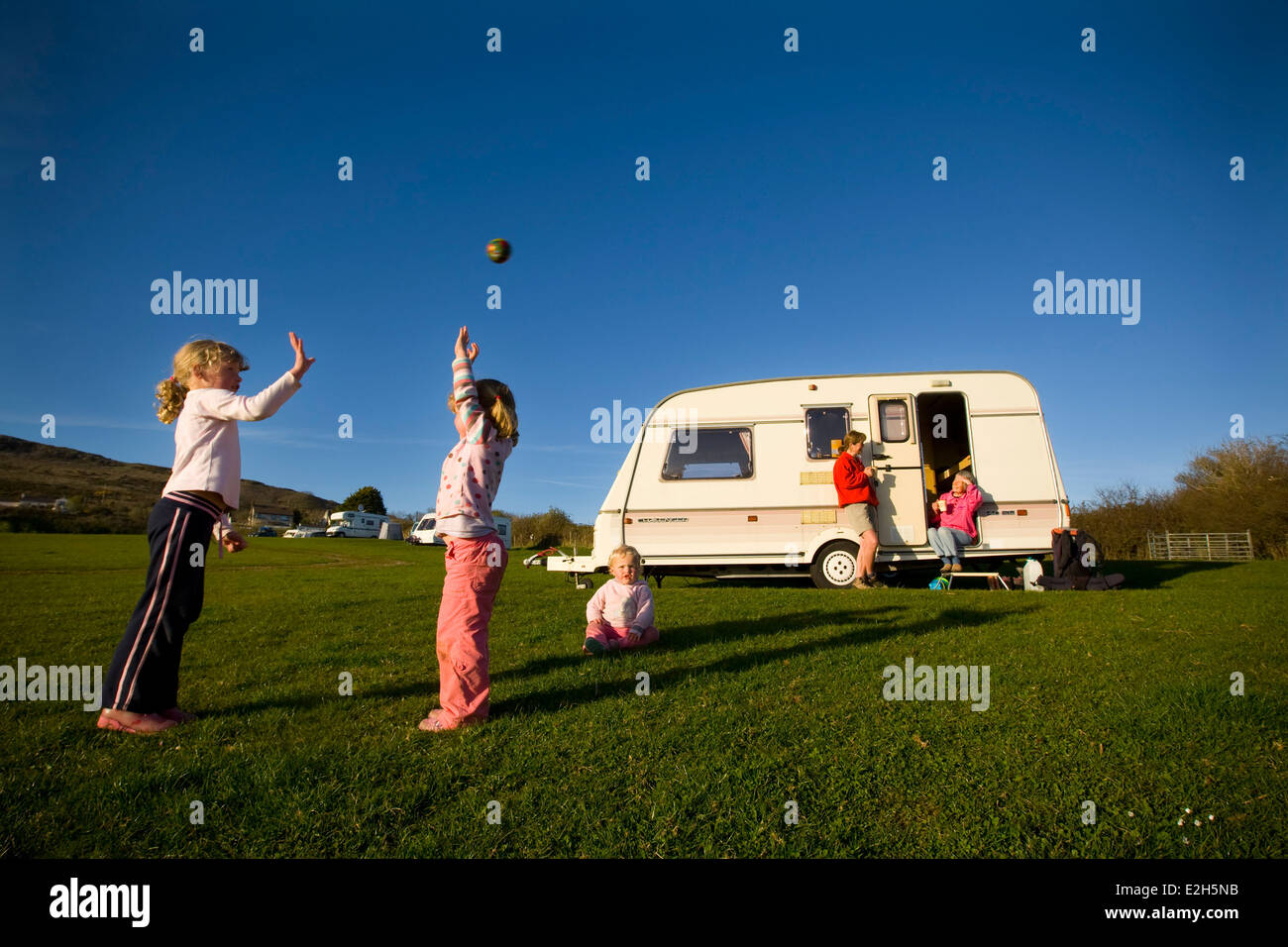 Caravaner's pitching for the night at a caravan site overlooking Oxwich Bay for the night. - Stock Image