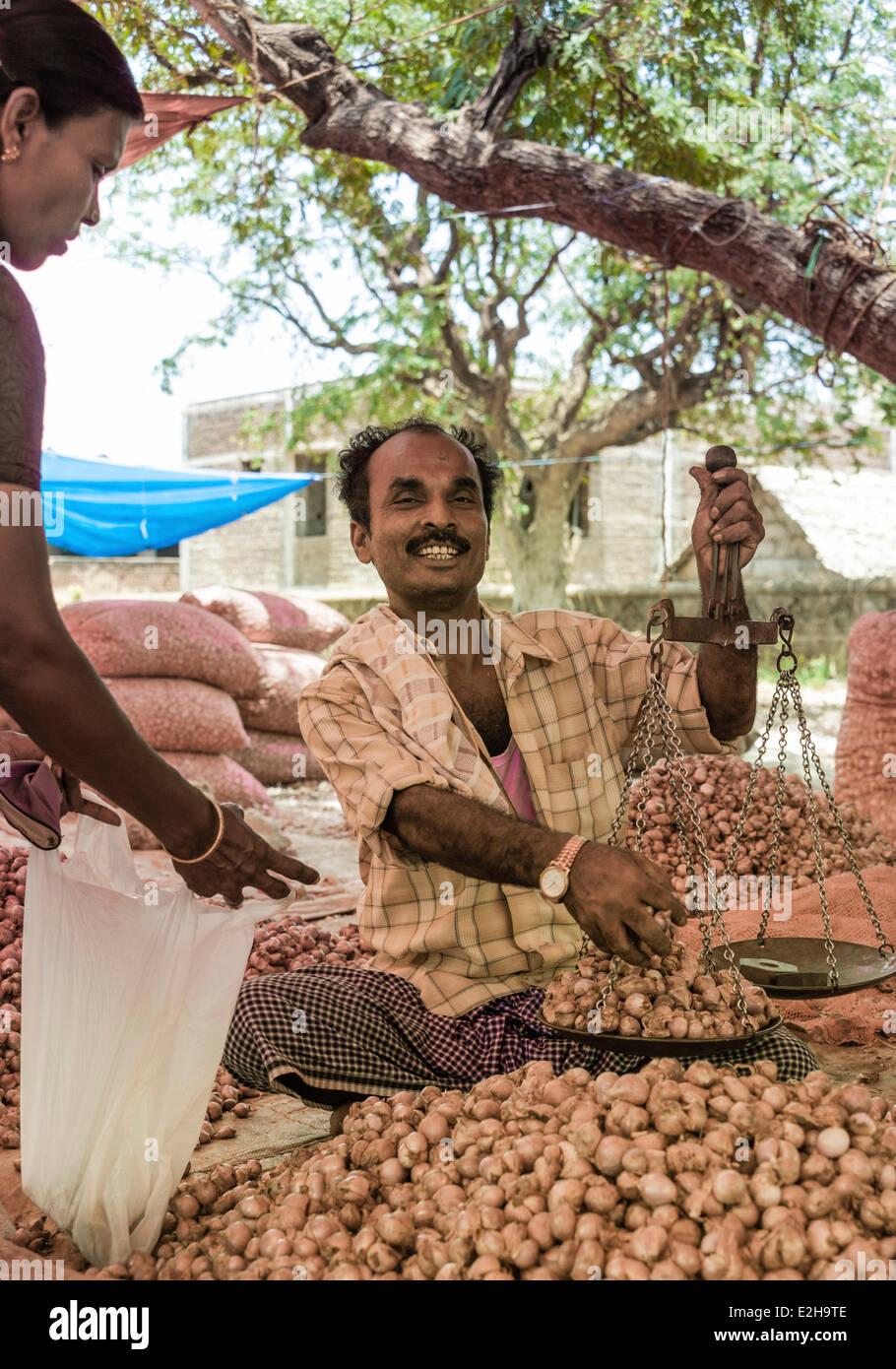 Cheerful vendor holding scales, Indian market, Chinnamanur, Tamil Nadu, India - Stock Image