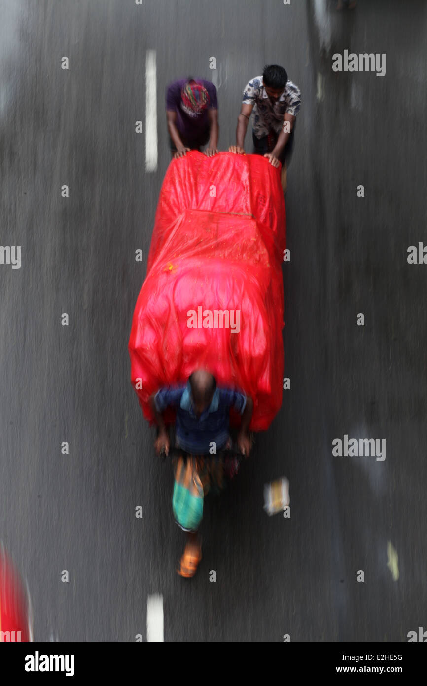 Three labor carrying good using wooden cart during rain. - Stock Image