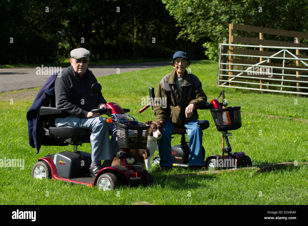 Two elderly men enjoy a trip out on their disability scooters in the sunshine. - Stock Image