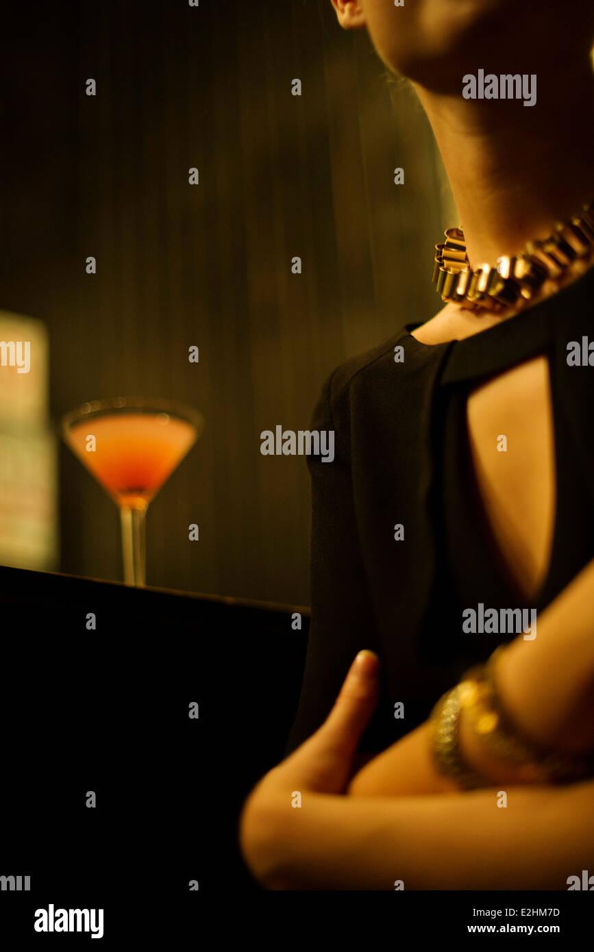Woman sitting alone at night club bar - Stock Image