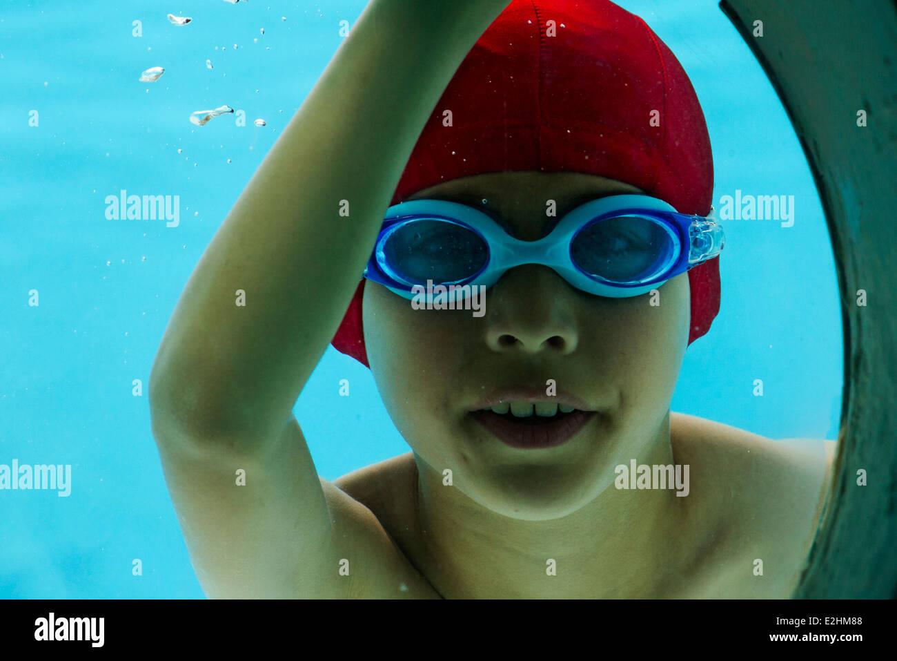 Boy underwater, looking through porthole, portrait - Stock Image
