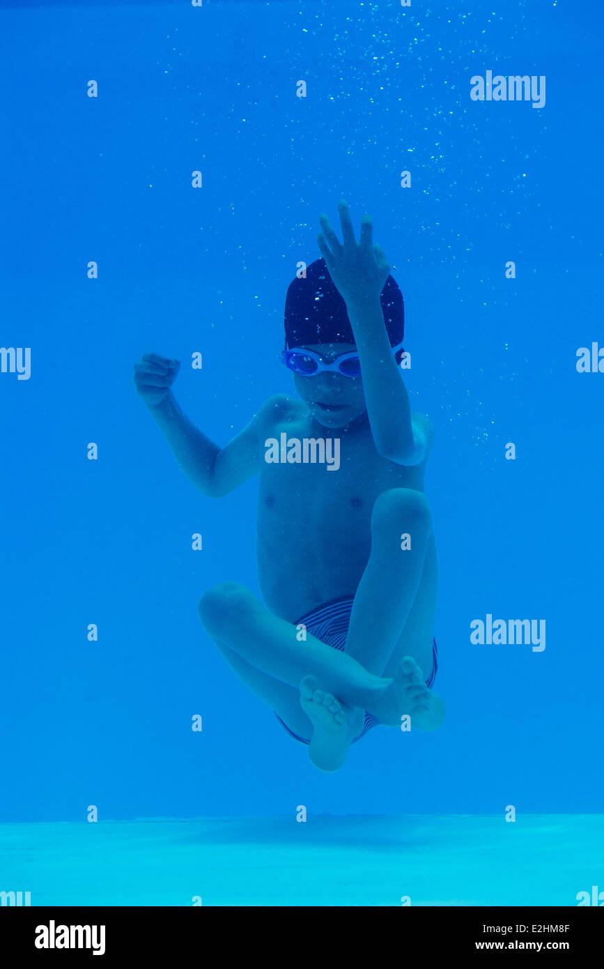 Boy sinking underwater in swimming pool - Stock Image