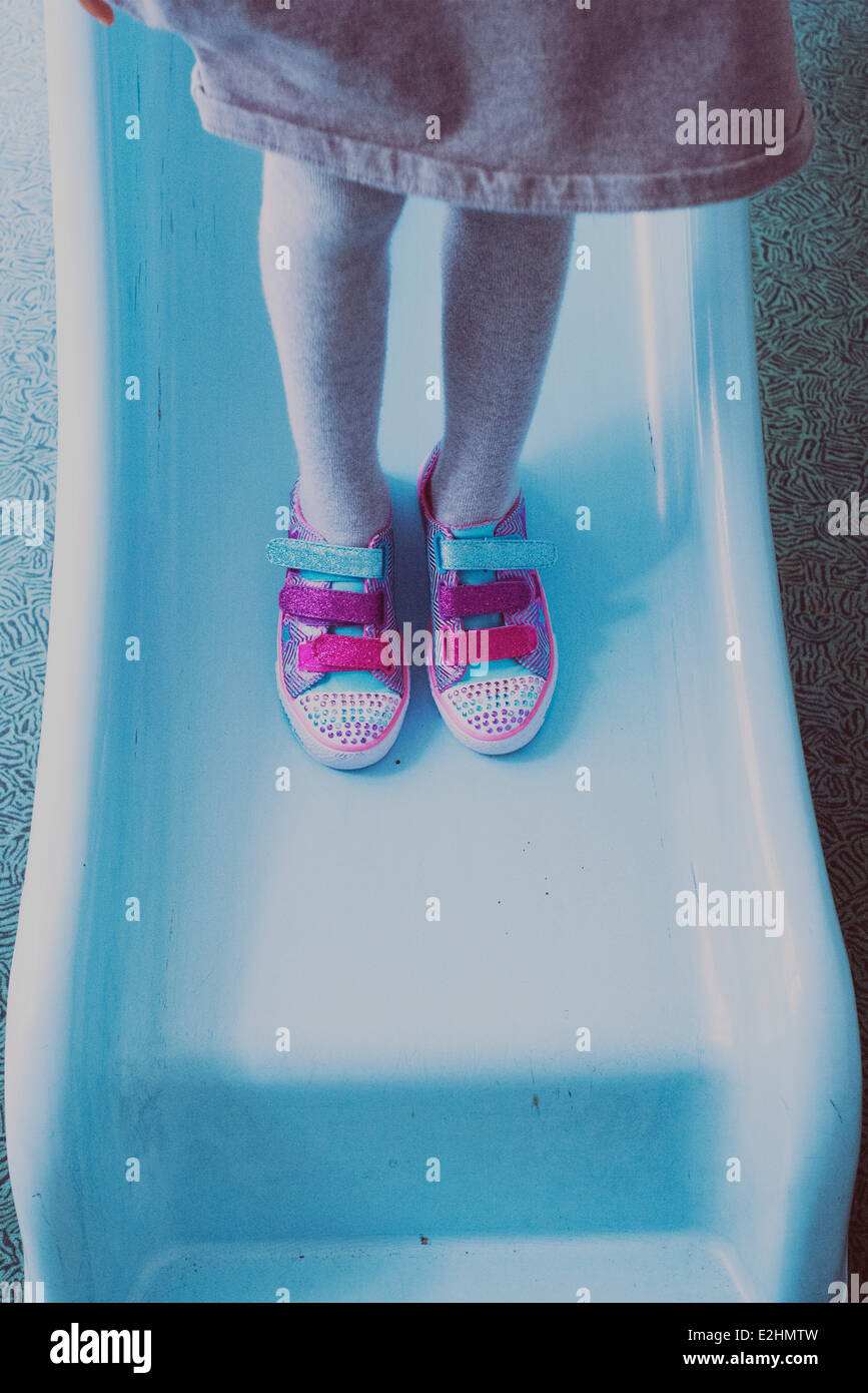 Girl standing on slide, wearing colorful sneakers, low section - Stock Image