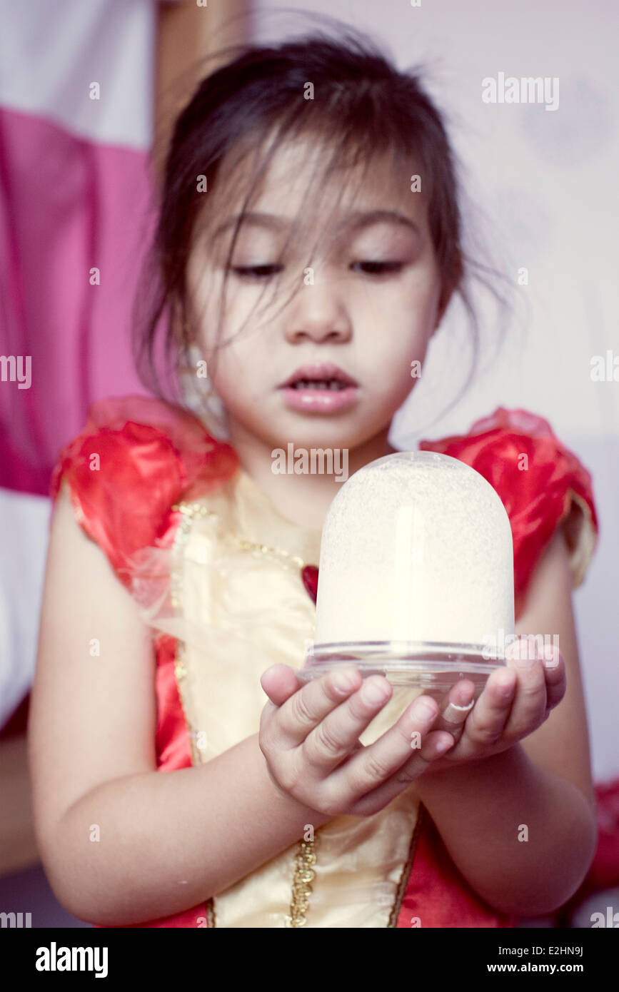 Little girl looking at snow globe - Stock Image