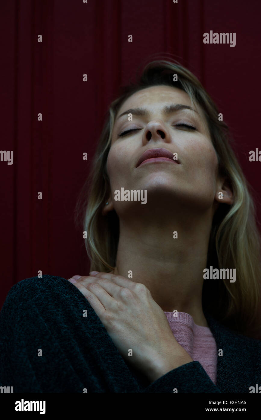Woman rubbing sore shoulder - Stock Image