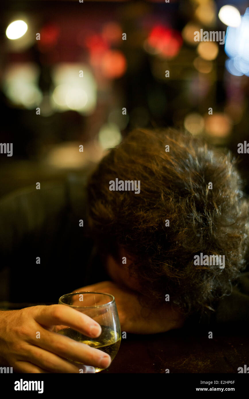 Man at bar with glass of whisky resting head on arms - Stock Image